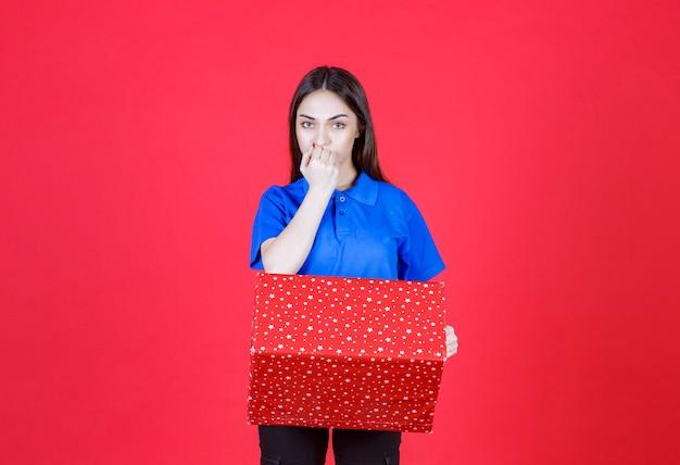 Vrouw met een rode geschenkdoos met witte stippen erop en kijkt verward en aarzelend.