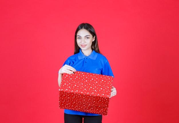 Vrouw met een rode geschenkdoos met witte stippen erop.