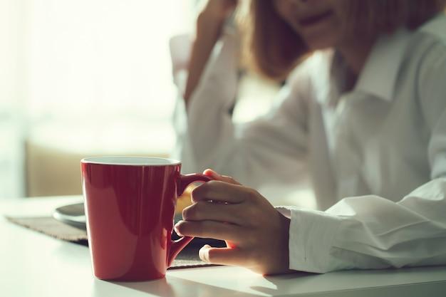 Vrouw met een rode koffiekopje in de ochtend