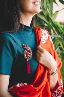 Vrouw met een rode pin met stenen