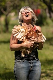 Vrouw met een roodharige leghen in haar armen in een grasveld