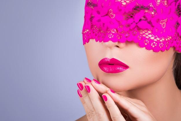 Vrouw met een roze blinddoek op haar gezicht