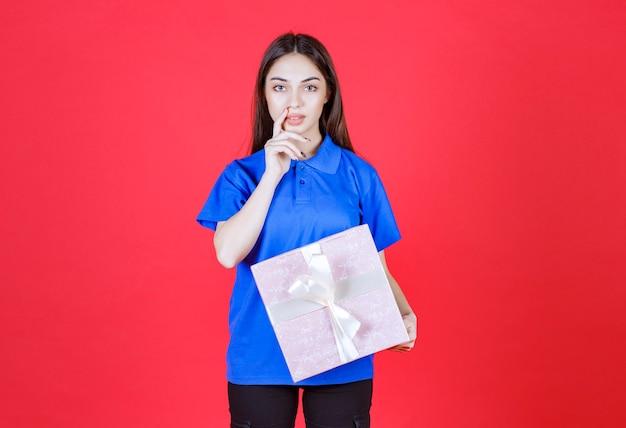 Vrouw met een roze geschenkdoos vastgebonden met wit lint en ziet er verward uit of heeft een goed idee.