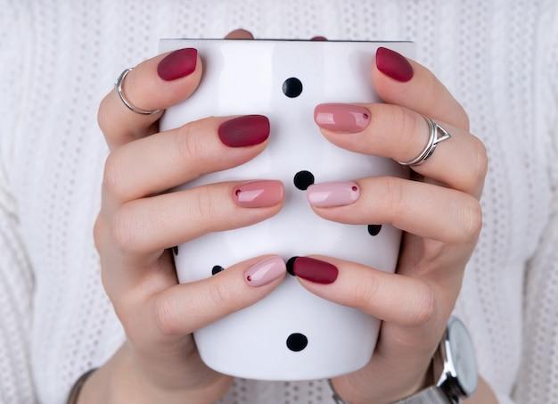 Vrouw met een roze manicure in minimalistische stijl met een kopje koffie of thee