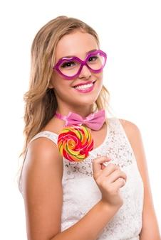 Vrouw met een roze vlinderdas, grappige glazen en snoep.