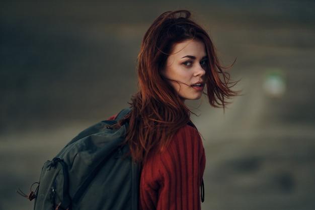 Vrouw met een rugzak in een rode trui in de bergen keerde terug en kapets