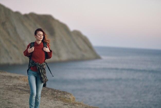 Vrouw met een rugzak op haar rug loopt in de natuur in de buurt van de zee in de bergen