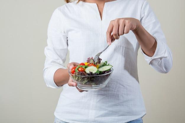 Vrouw met een salade en een vork in de hand