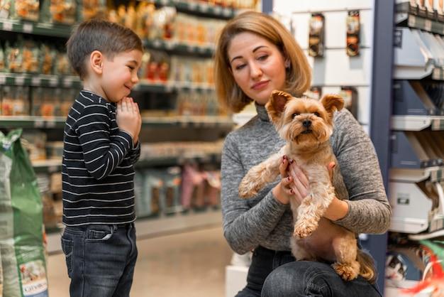 Vrouw met een schattige kleine hond in de dierenwinkel