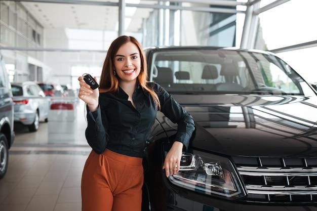 Vrouw met een sleutel in de buurt van haar nieuwe auto