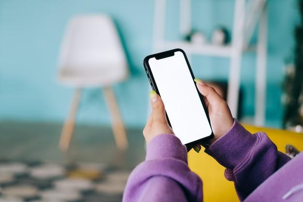 Vrouw met een smartphone met een wit scherm mock-up, rustend op de fauteuil in de huiskamer.