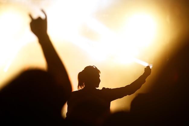Vrouw met een smartphone tijdens een concert