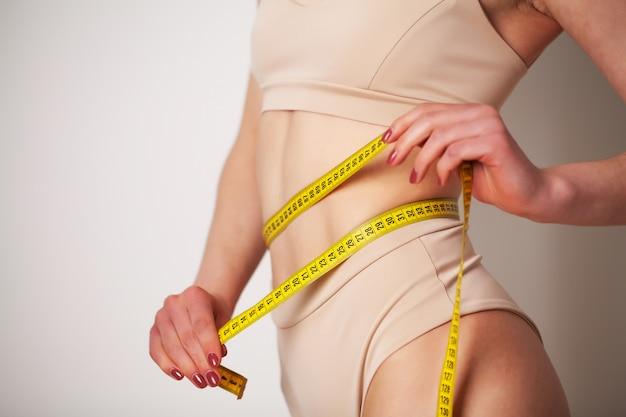 Vrouw met een sportief figuur meet de grootte van haar taille