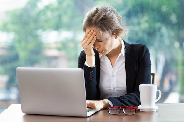 Vrouw met een sterke hoofdpijn met een laptop en een kopje koffie