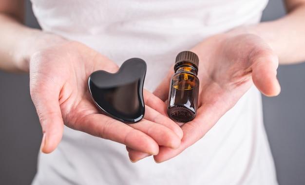Vrouw met een stimulator, een gouacheschraper en een fles biologische aromatische olie