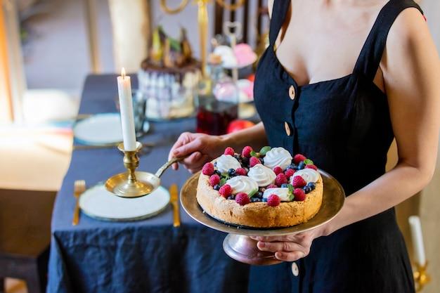Vrouw met een taart in de buurt van een tafel met kaarsen