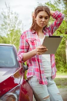 Vrouw met een tablet in handen die zich naast de auto bevinden
