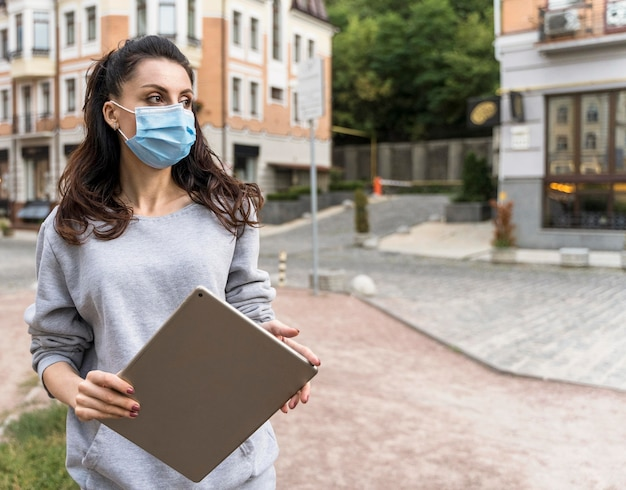 Vrouw met een tablet terwijl ze een medisch masker met kopie ruimte draagt