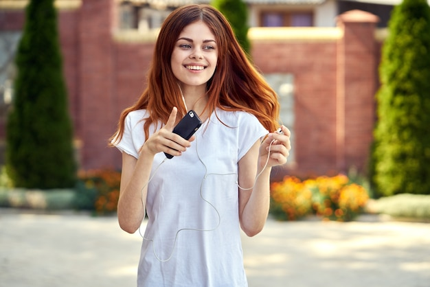 Vrouw met een telefoon en hoofdtelefoons