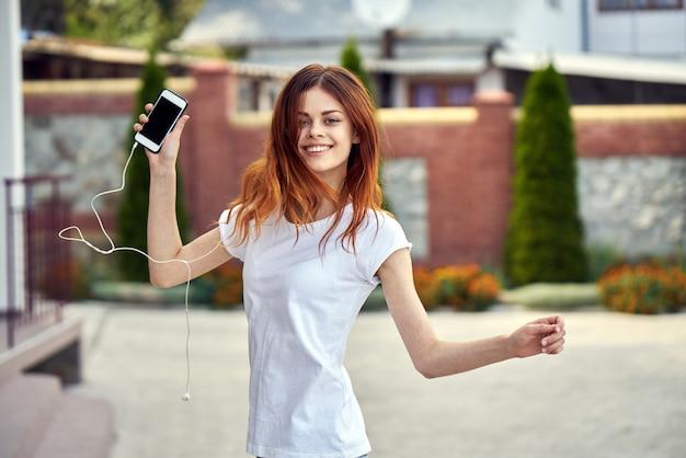 Vrouw met een telefoon in hoofdtelefoon loopt