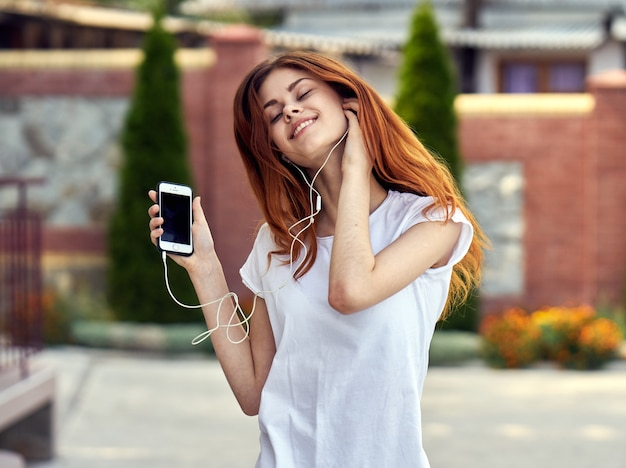 Vrouw met een telefoon in hoofdtelefoons loopt