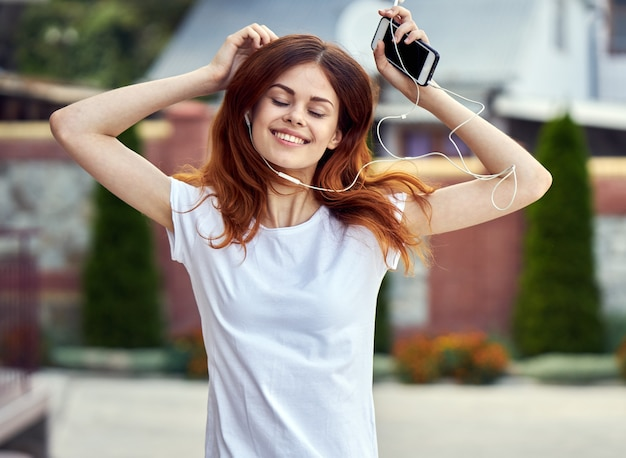Vrouw met een telefoon luisteren naar muziek en dansen