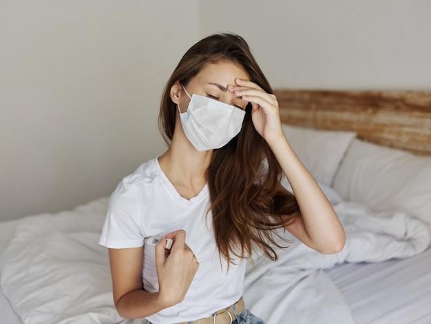 Vrouw met een thermometer in de handen van een slaapkamer met een medisch masker