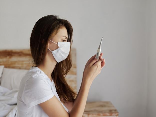 Vrouw met een thermometer in haar handen in een slaapkamer met een medisch masker