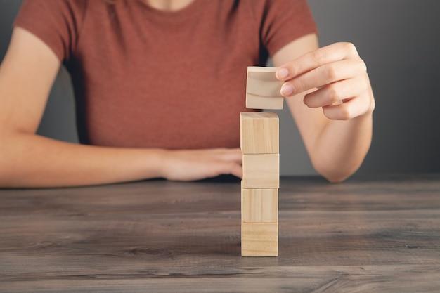 Vrouw met een toren van houten kubussen