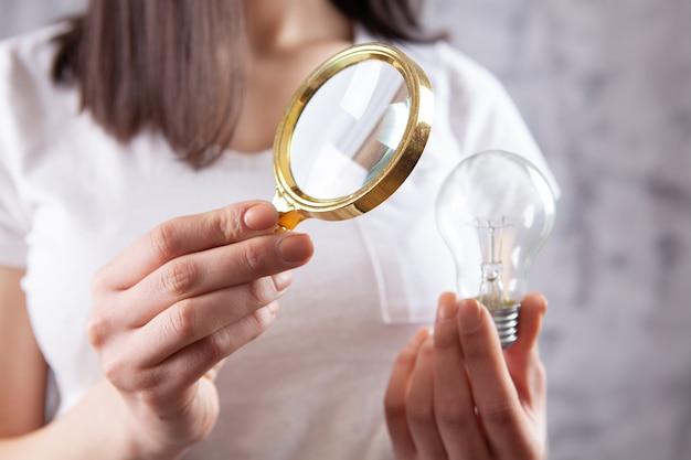 Vrouw met een vergrootglas kijkt naar een gloeilamp. concept studie idee