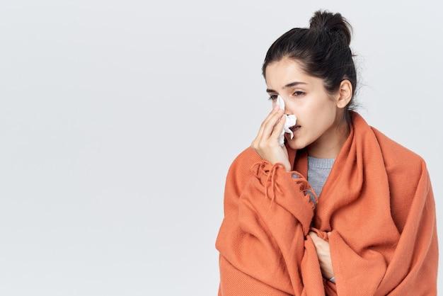 Vrouw met een verkoudheid veegt haar neus af met een zakdoek griep