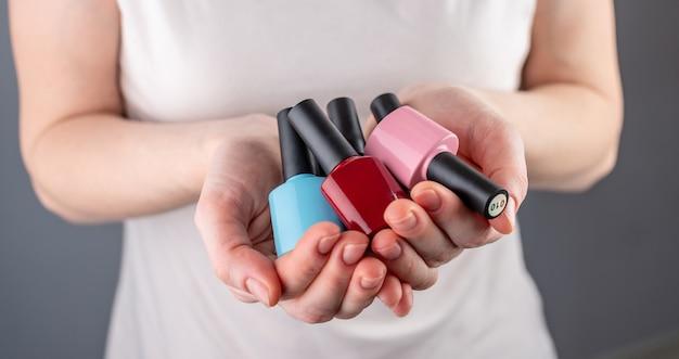 Vrouw met een verscheidenheid aan kleurrijke flessen nagellak in haar handen