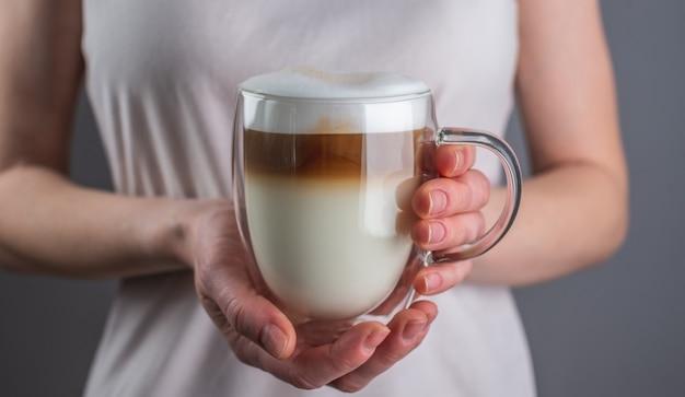 Vrouw met een verse, aromatische latte-koffie, in lagen gegoten in een doorzichtige dubbele glazen beker