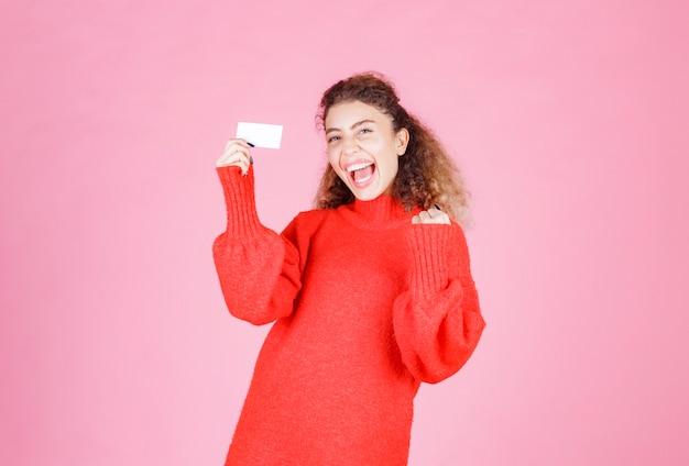 Vrouw met een visitekaartje ziet er erg blij en verrast uit.