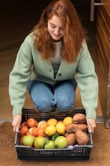 Vrouw met een voedselmand die bij haar deur werd afgeleverd