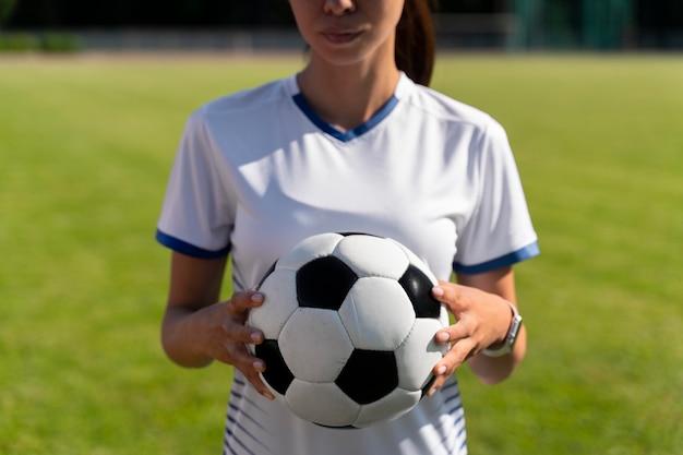 Vrouw met een voetbal op het veld