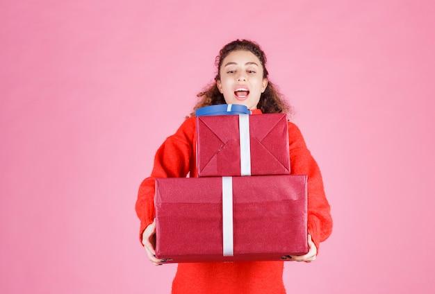Vrouw met een voorraad grote geschenkdozen.