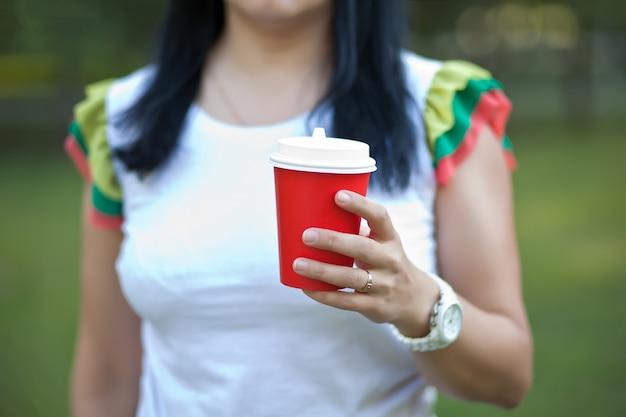 Vrouw met een wegwerp papieren kopje koffie buiten.
