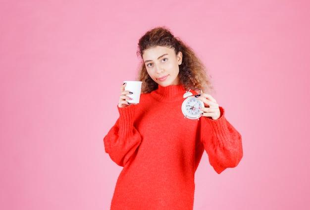 Vrouw met een wekker en een kopje koffie wijzend op haar ochtendroutine.