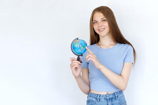 Vrouw met een wereldbol die lacht op een witte achtergrond