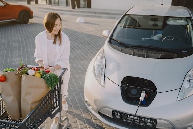 Vrouw met een winkelwagentje door haar auto