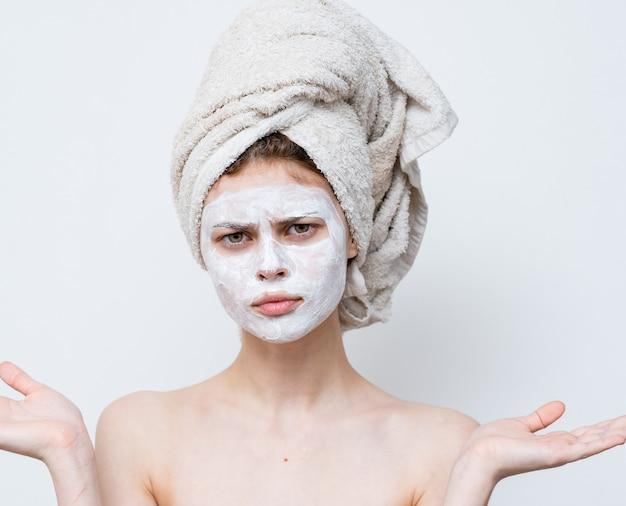 Vrouw met een wit masker tegen zwarte stippen op haar gezicht en een handdoek op haar hoofd