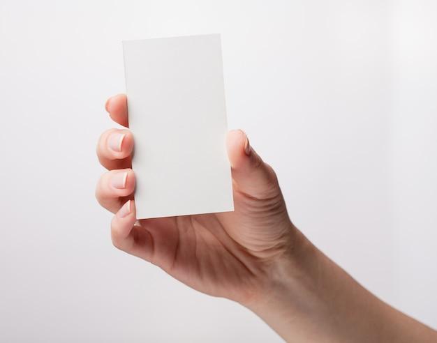 Vrouw met een wit visitekaartje in zijn hand, close-up