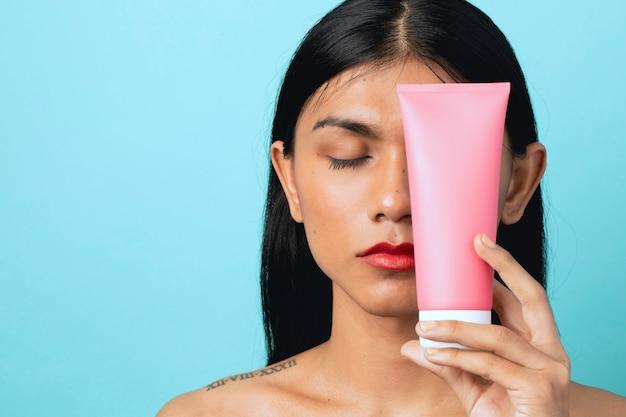 Vrouw met een witte gezichtscrèmecontainer
