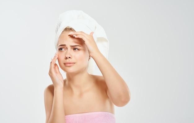Vrouw met een witte handdoek op haar hoofd raakt haar gezicht met haar handen op een lichte achtergrond