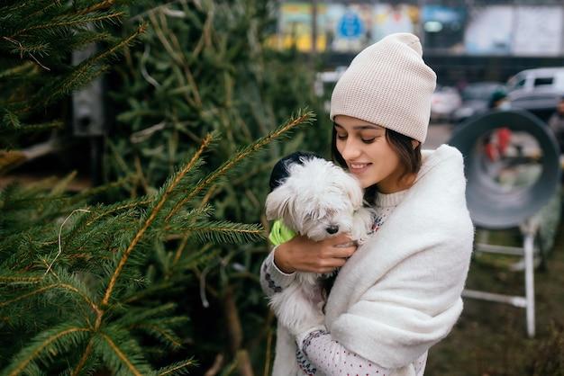 Vrouw met een witte hond in haar armen dichtbij een groene kerstbomen op de markt