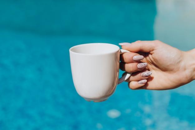 Vrouw met een witte koffiekop bij het zwembad