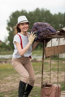 Vrouw met een zak fruit op een boerderij