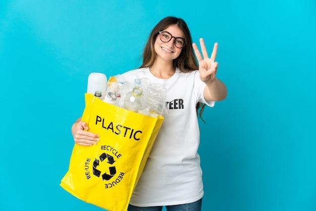 Vrouw met een zak vol flessen om te recyclen op blauw gelukkig en drie tellen met vingers