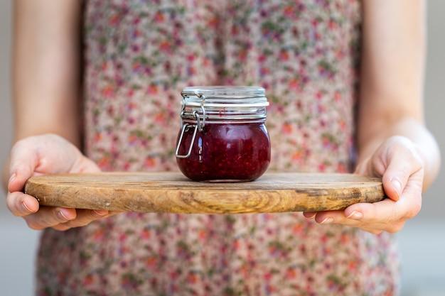 Vrouw met een zelfgemaakte veganistische rauwe frambozenjam in een glazen pot op een houten oppervlak